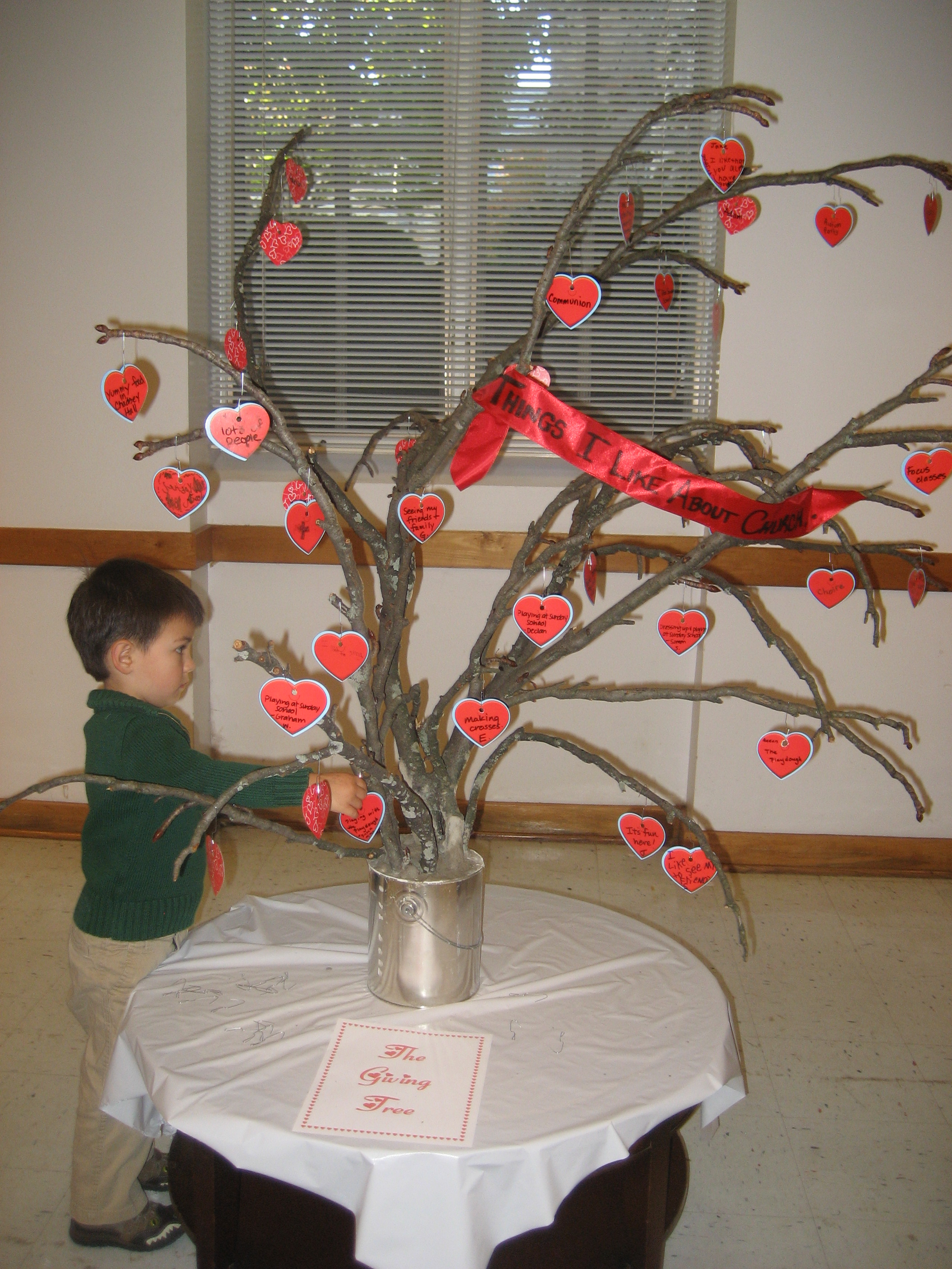 Child hangs a heart on the Giving Tree